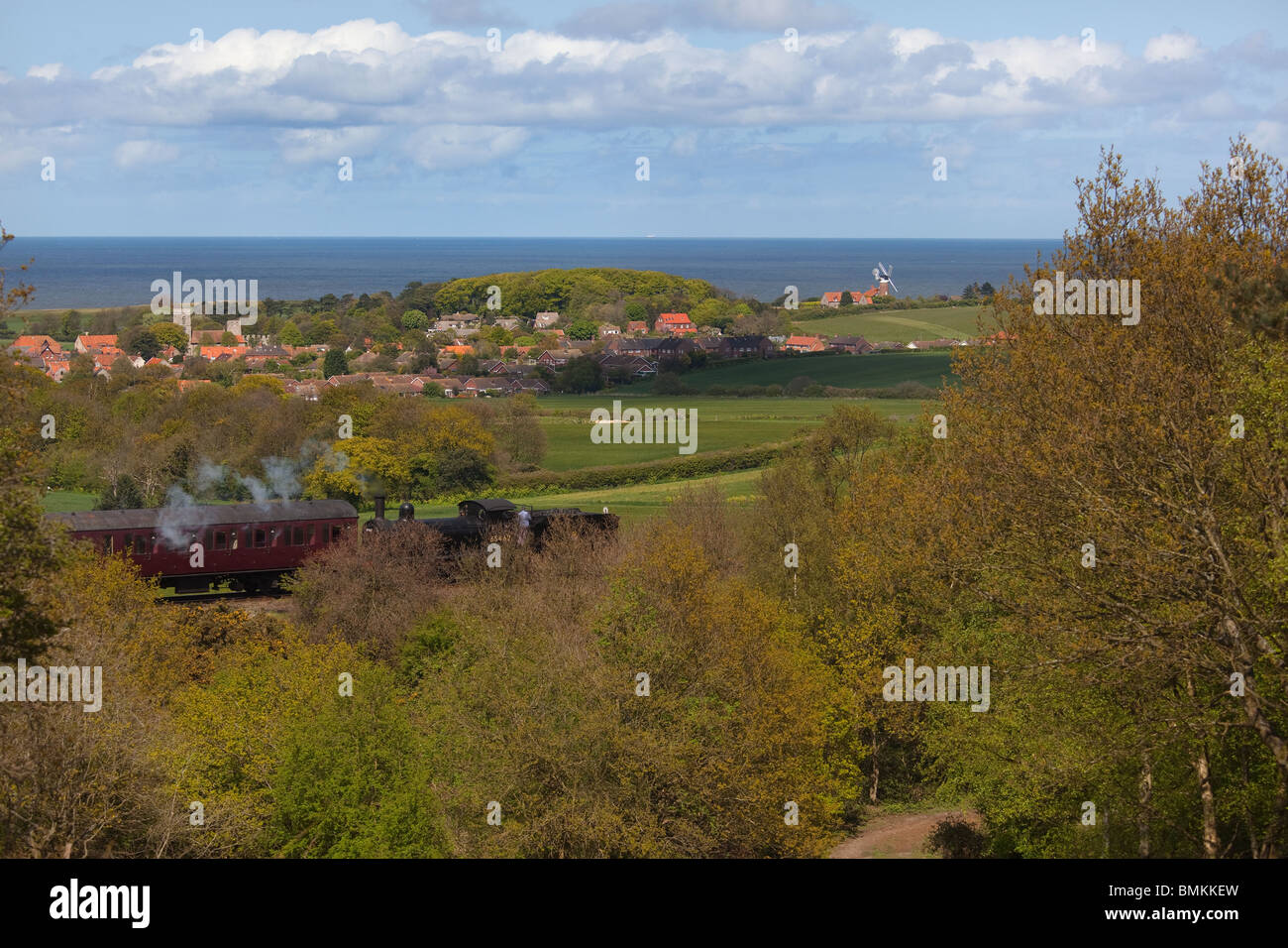 Weybourne Village from Kelling Heath Nature Reserve and passing steam train Stock Photo