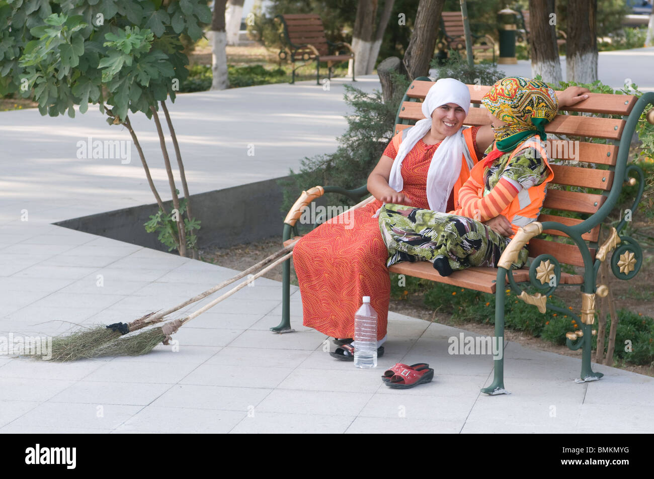 Young, happy women at bench, Ashgabad, Turkmenistan - Stock Image
