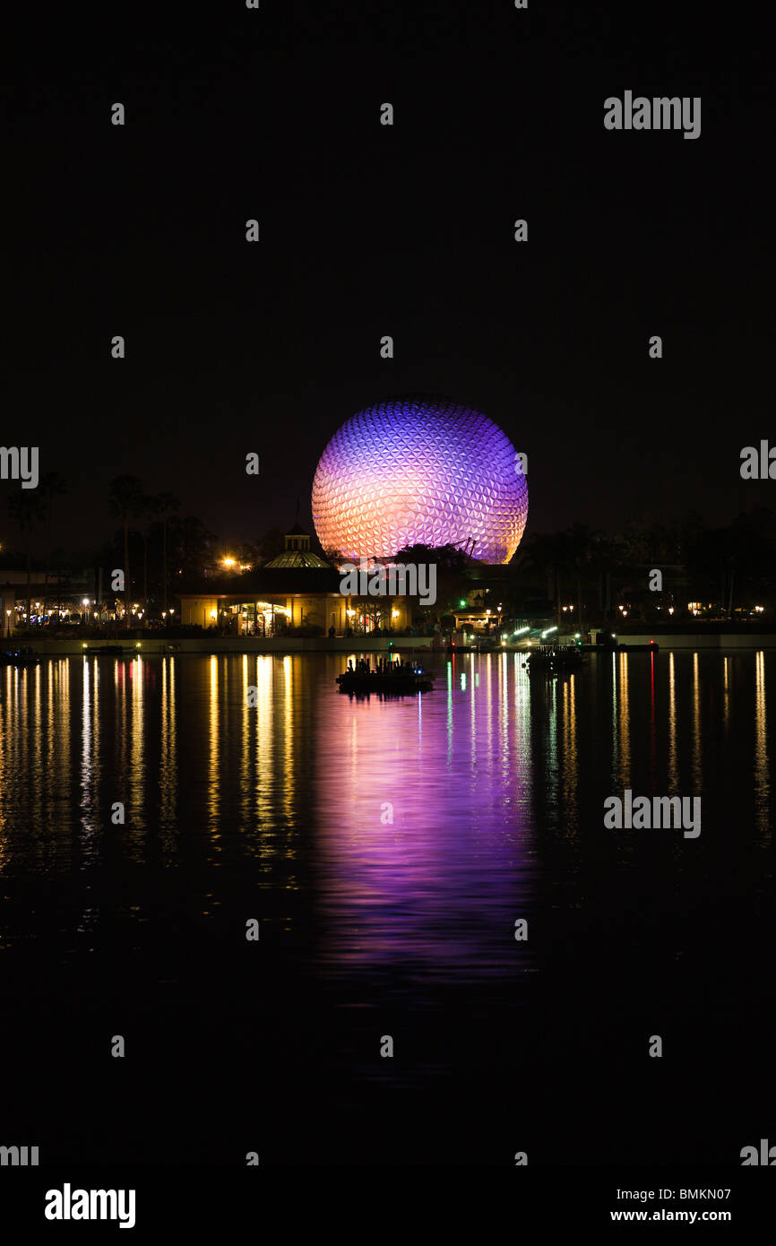 Geodesic dome of Spaceship Earth attraction lit with purple lights reflecting off lake at night in Walt Disney's - Stock Image