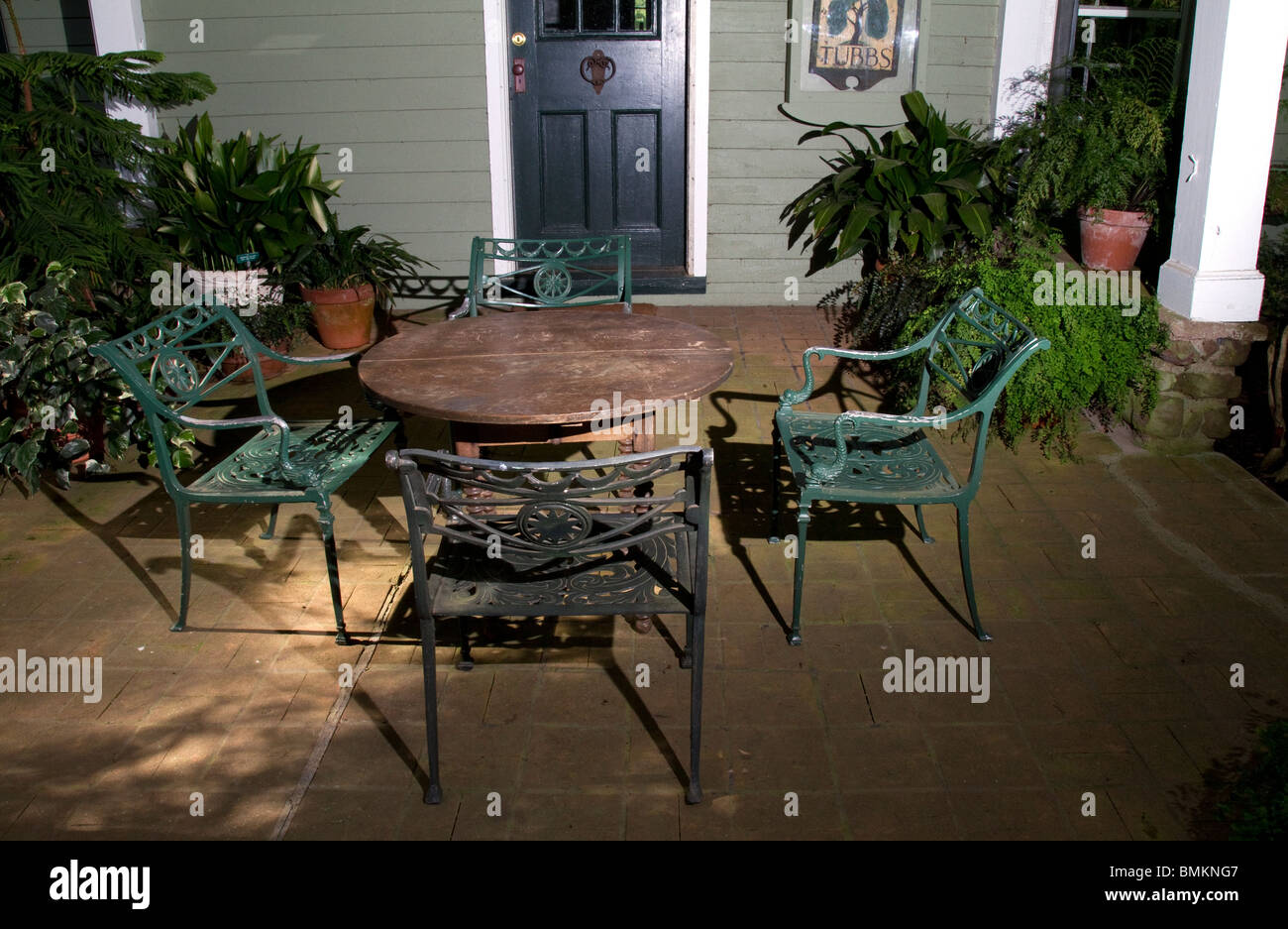 On the veranda four wrought iron chairs, a table and potted plants ...