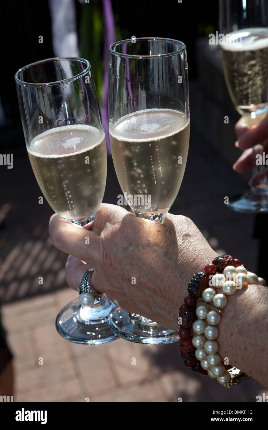 Detroit, Michigan - A woman holds glasses of champagne at a wedding. - Stock Image