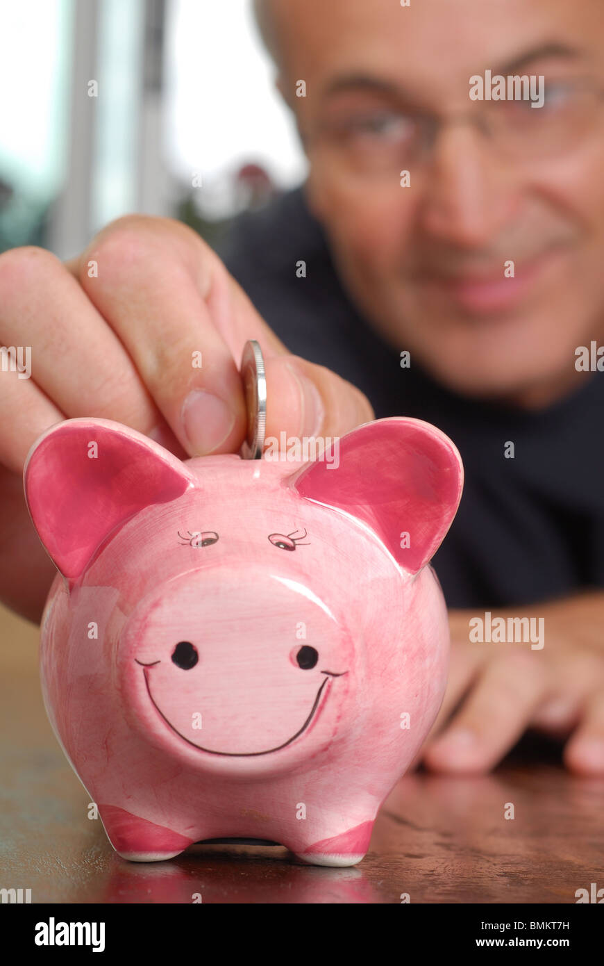 Man is trying to save some money by filling up piggy bank - Stock Image