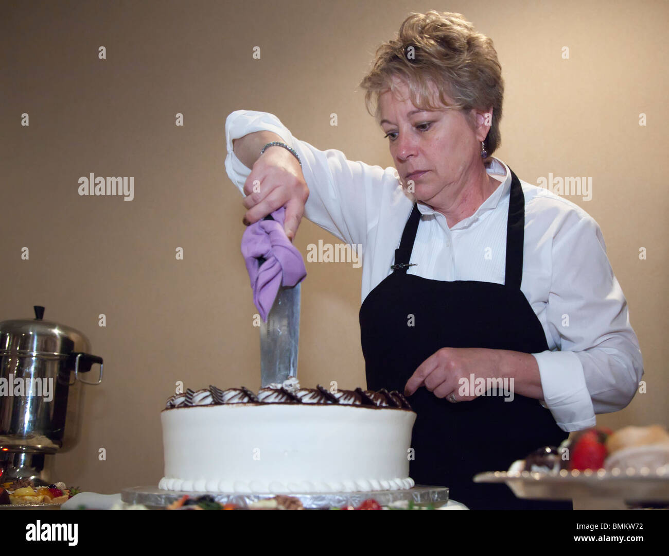 Detroit, Michigan - A catering employee cuts the cake at a wedding. - Stock Image