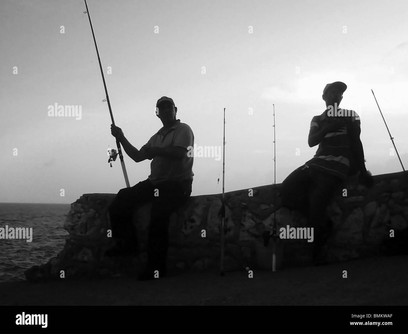 Men fish in the evening from the sea wall in Santo Domingo, Dominican Republic - Stock Image