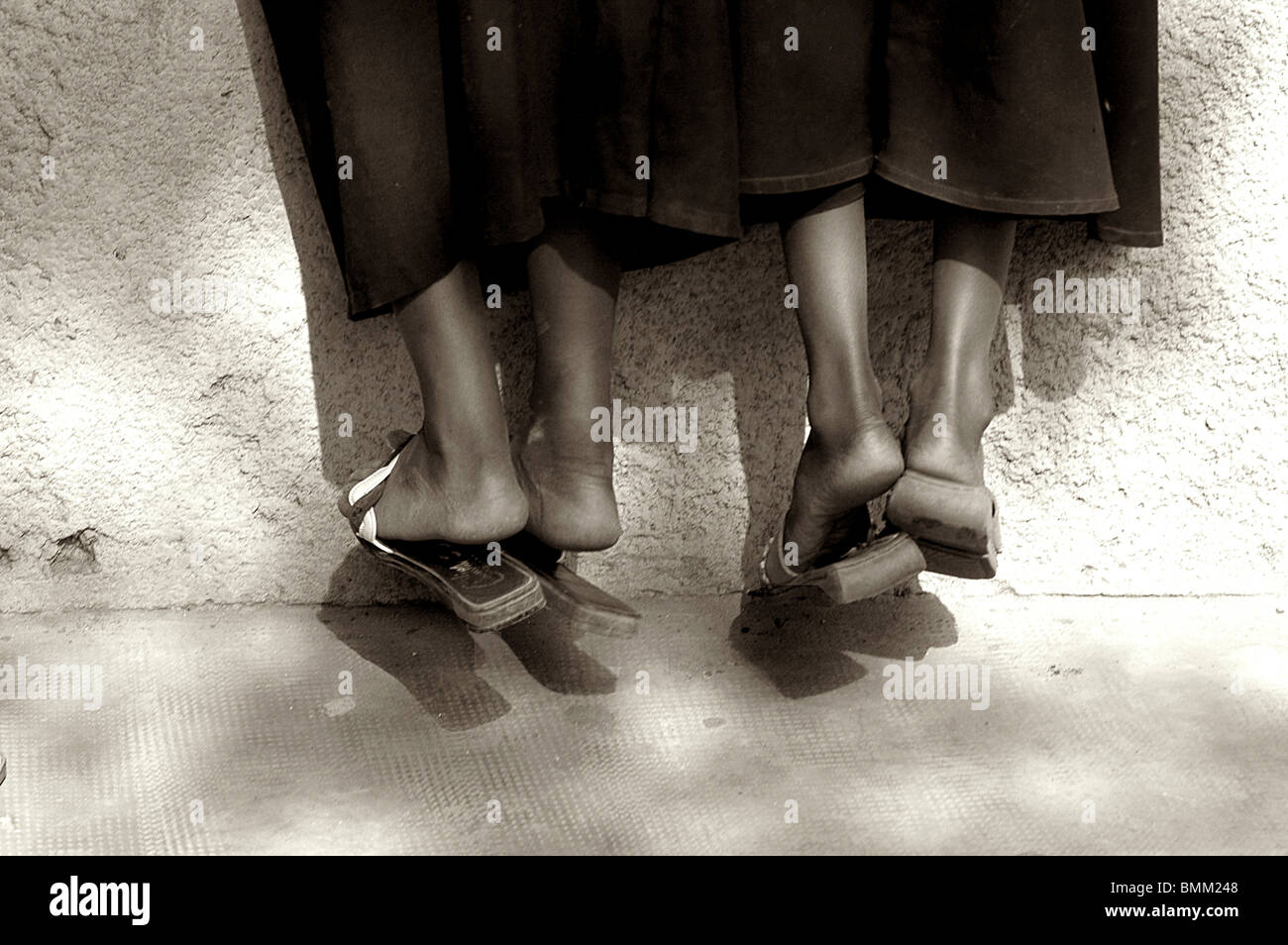 Niger, Niamey, Feet, plastic slippers and long black skirts of two african schoolgirls suspended. - Stock Image