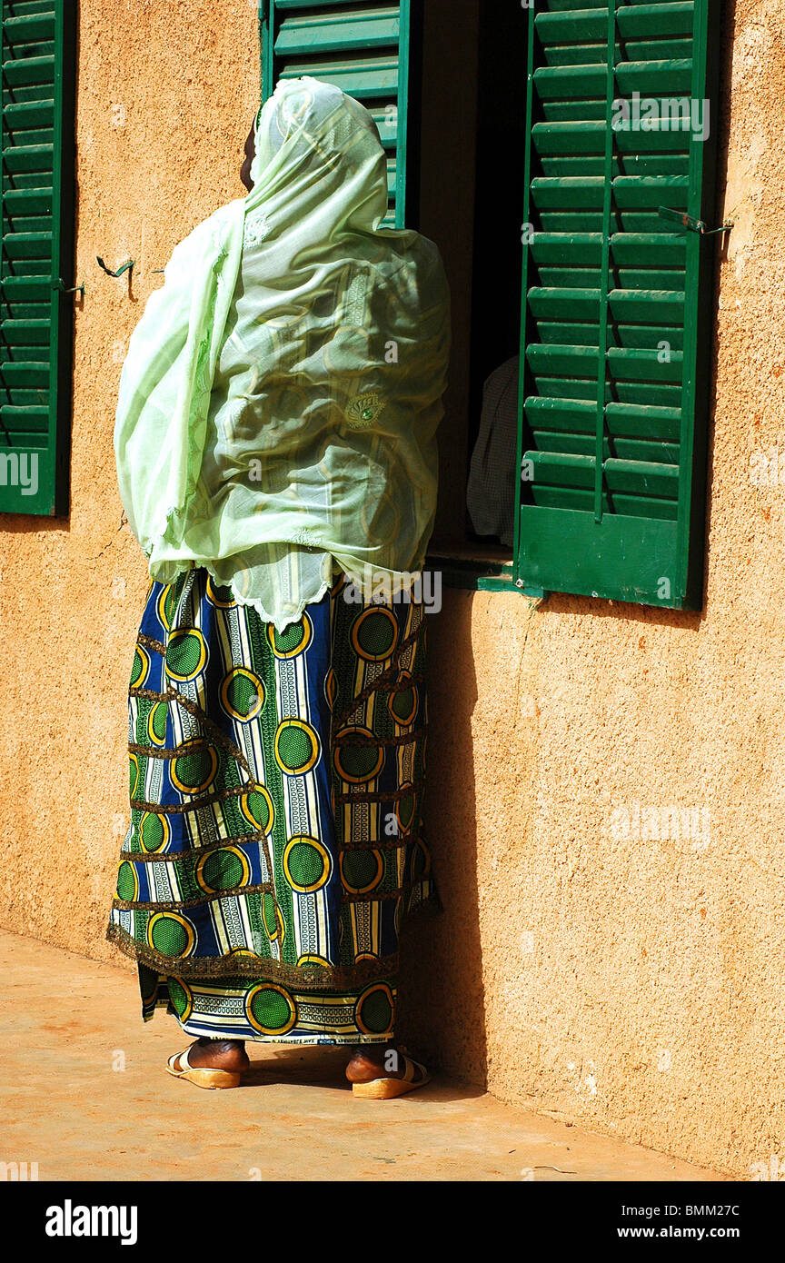 Niger, Niamey, African muslim woman in green traditional clothes, standing next to green window shutter - Stock Image