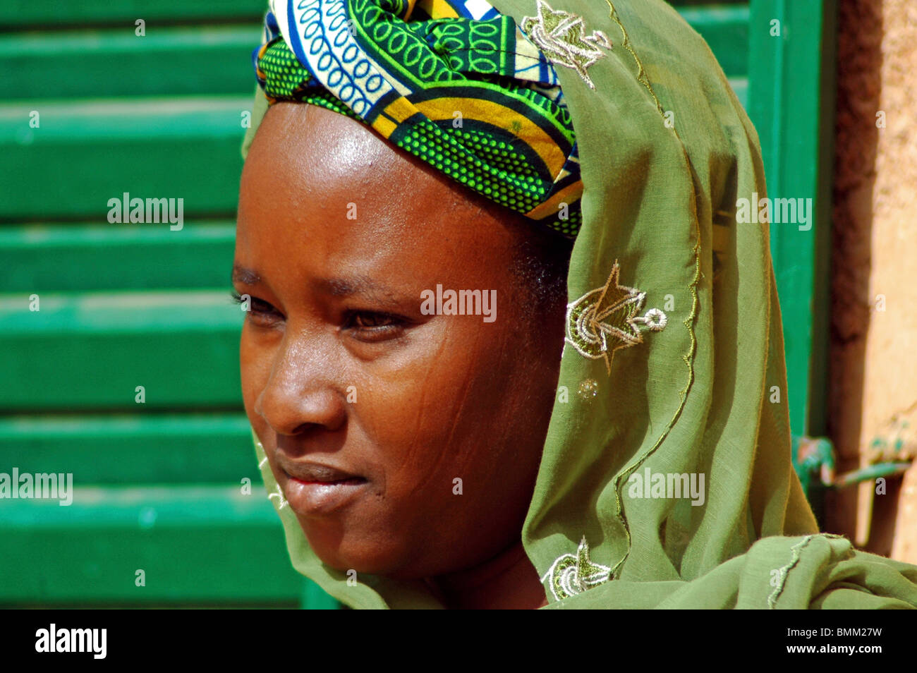 Niger, Niamey, Portrait of an african and muslim woman wearing a green scarf and standing next to a green window - Stock Image