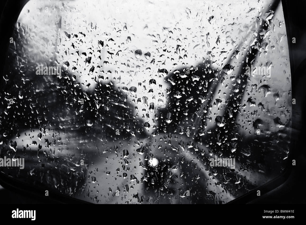 Raindrops of the car mirror on a gray lonely rainy day. - Stock Image