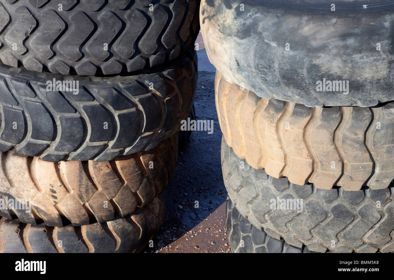 Piles of used front loader tyres - Stock Image