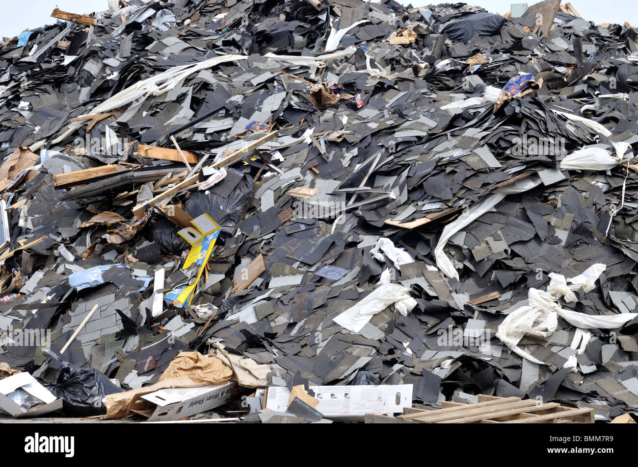 Big pile of asphalt roofing shingles and trash at landfill - Stock Image
