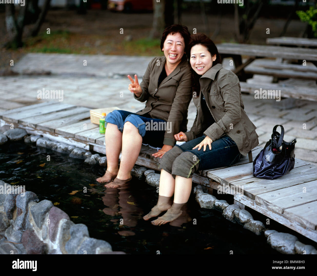 Japanese women soak the feet in warm waters at a Beppu onsen - Stock Image