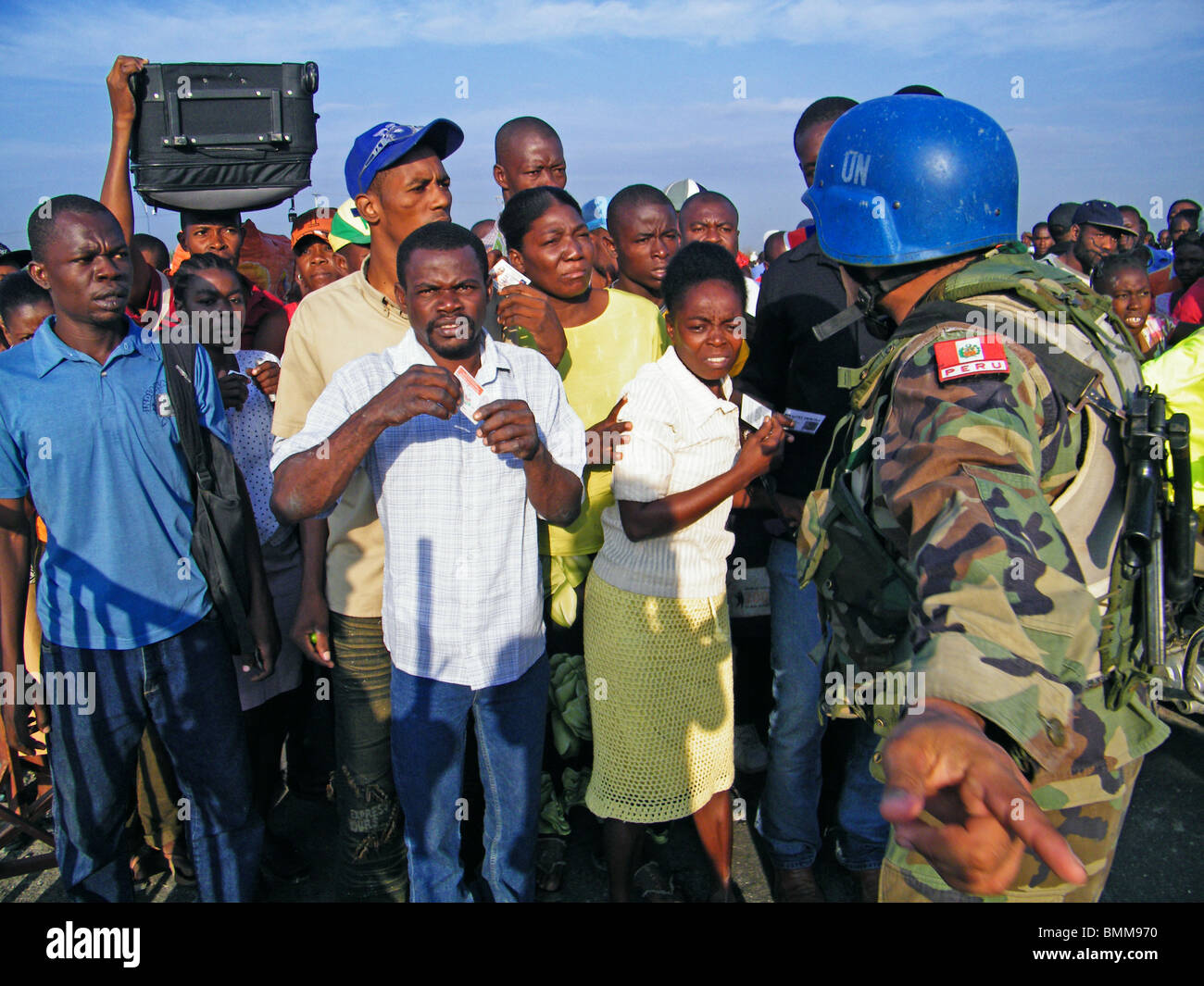 Crowds of earthquake survivors waiting for aid and trying to leave the city at a checkpoint in Port au Prince, Haiti - Stock Image
