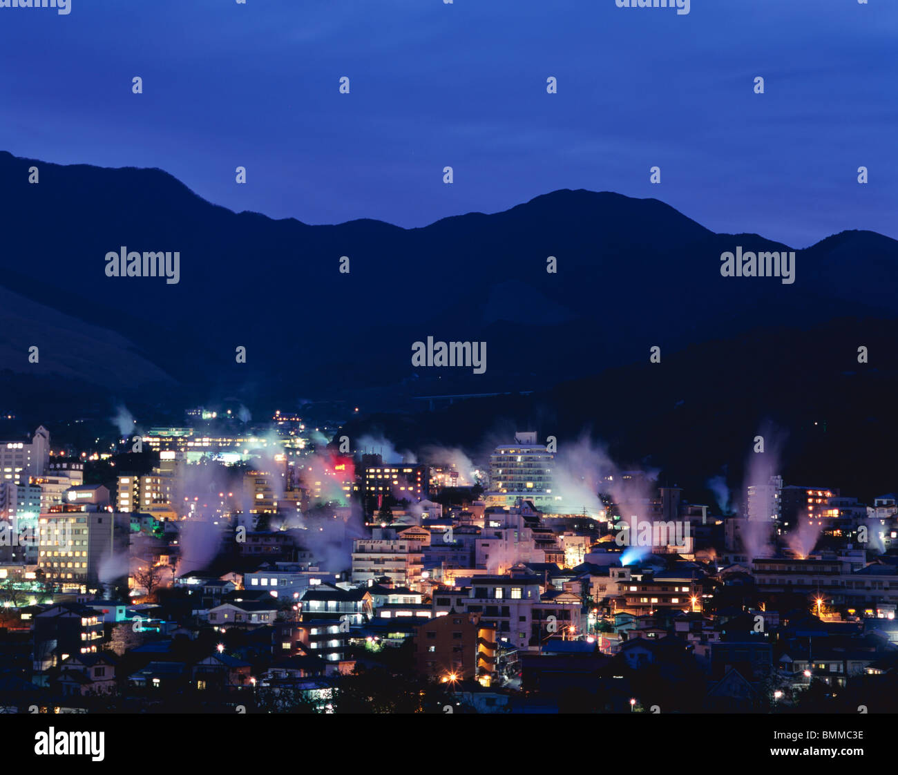 Twilight Beppu City. Steam plumes rise from onsen - Stock Image