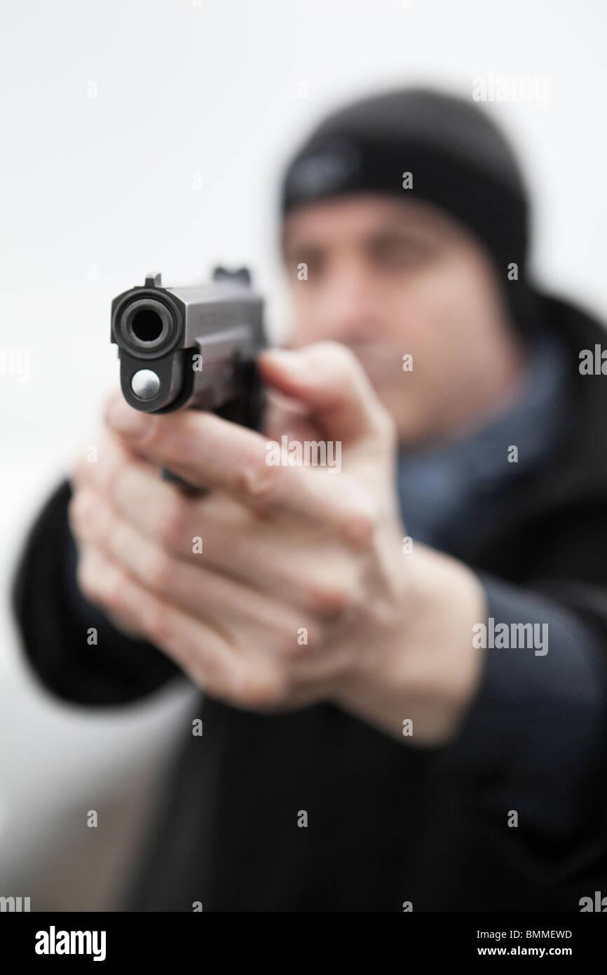 Man pointing a loaded handgun - Stock Image