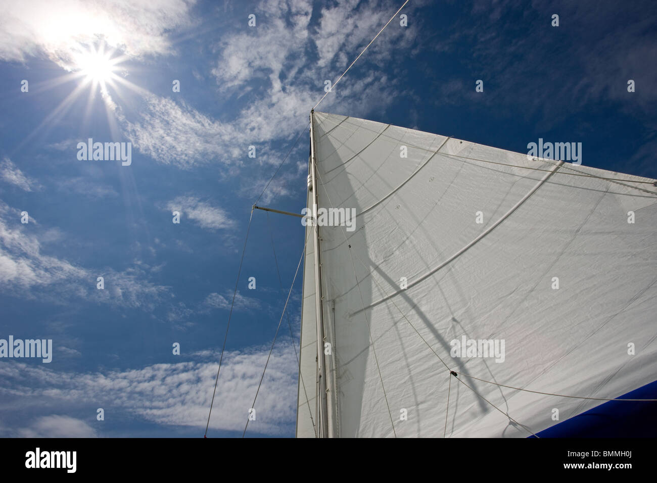 Sun shining down on the sails of a yacht - Stock Image