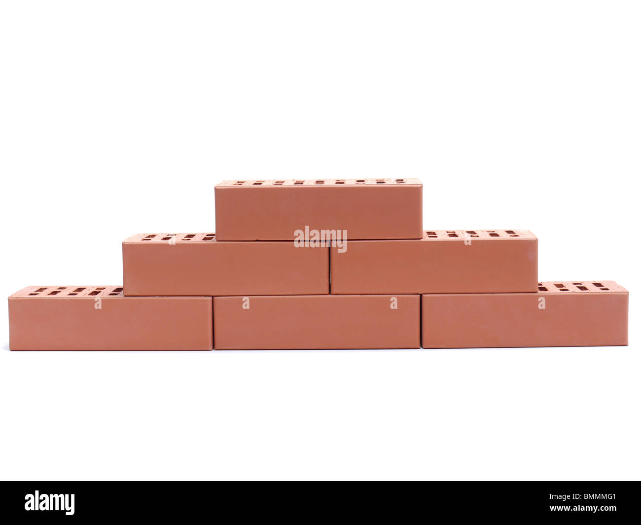 Partial wall made of perforated bricks over white background - Stock Image