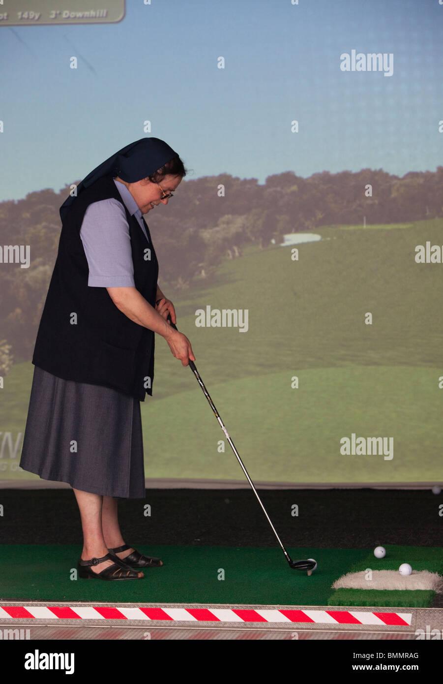 Full length portrait of a nun playing virtual golf, London, England, UK - Stock Image