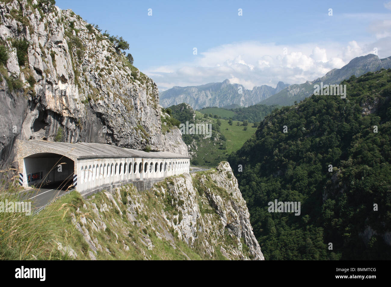 Road tunnel high in the Picos de Europa on the AS-114 near Ortiguero, Asturias, Spain, with forested hillside and - Stock Image