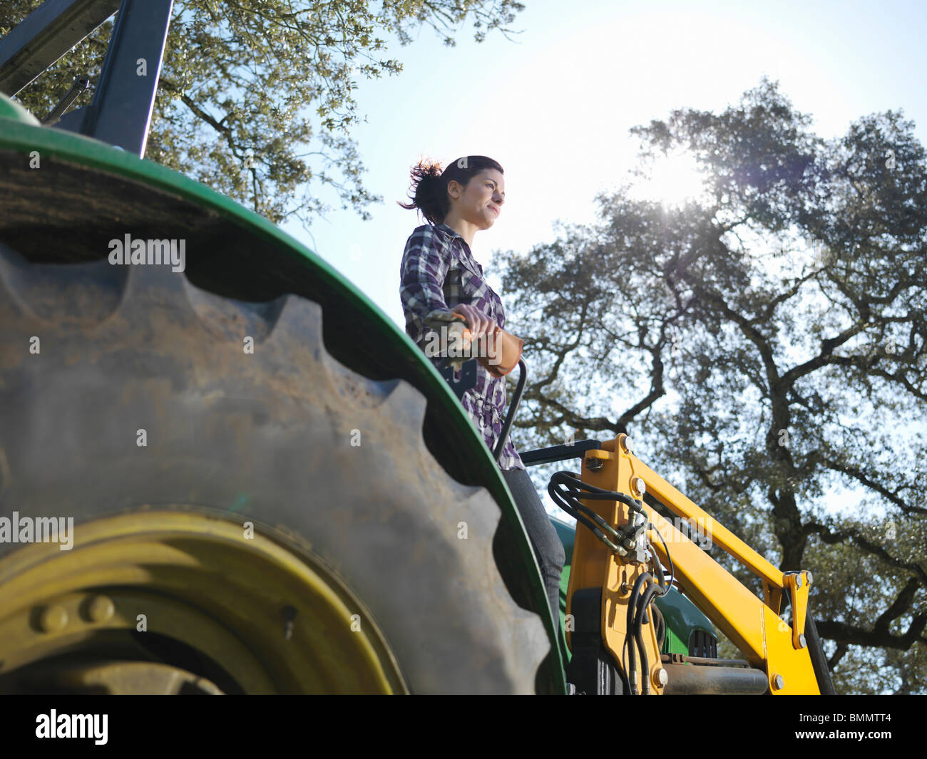 Woman standing on tractor looking out - Stock Image