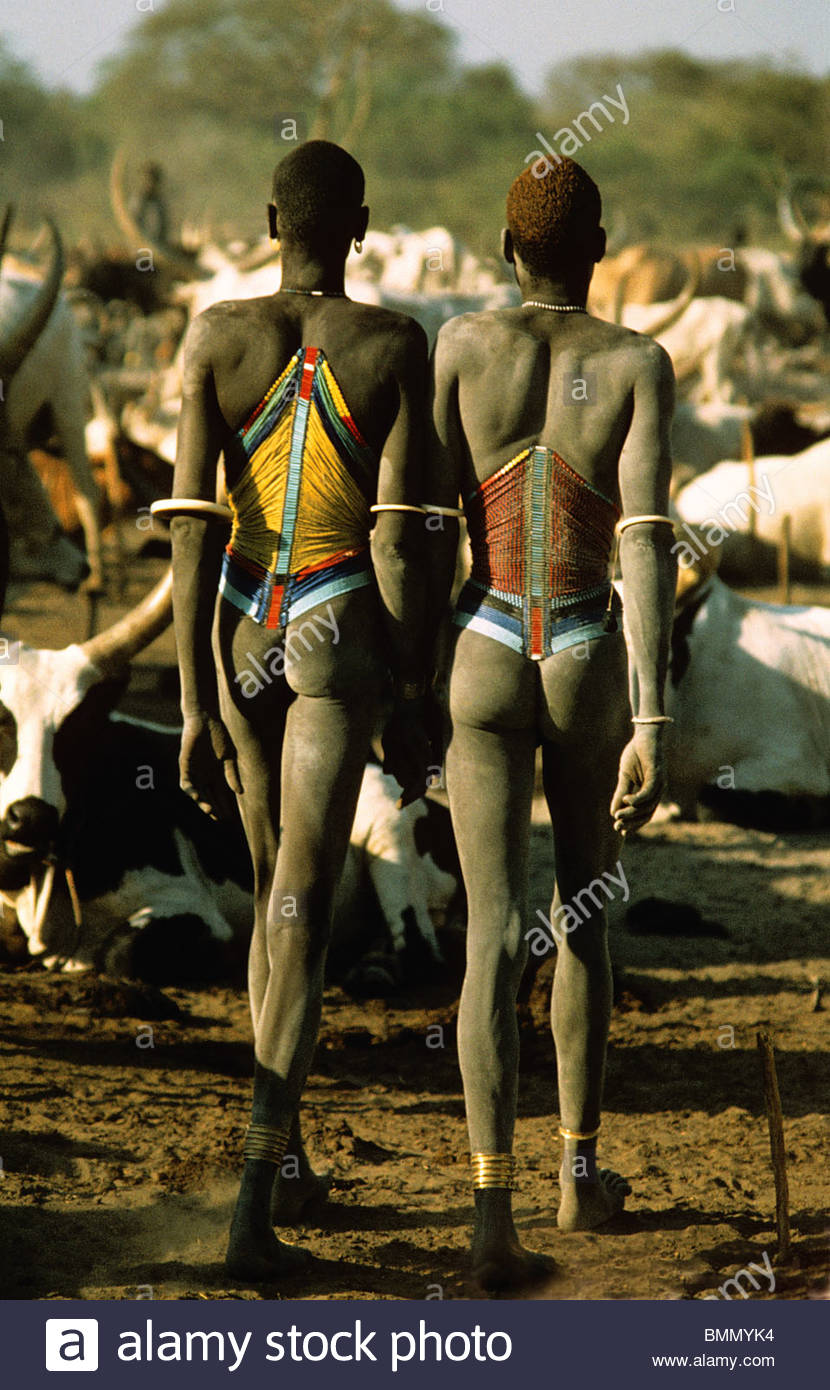 Dinka cattle herders wearing traditional beaded corsets and ivory armlets. Southern Sudan - Stock Image