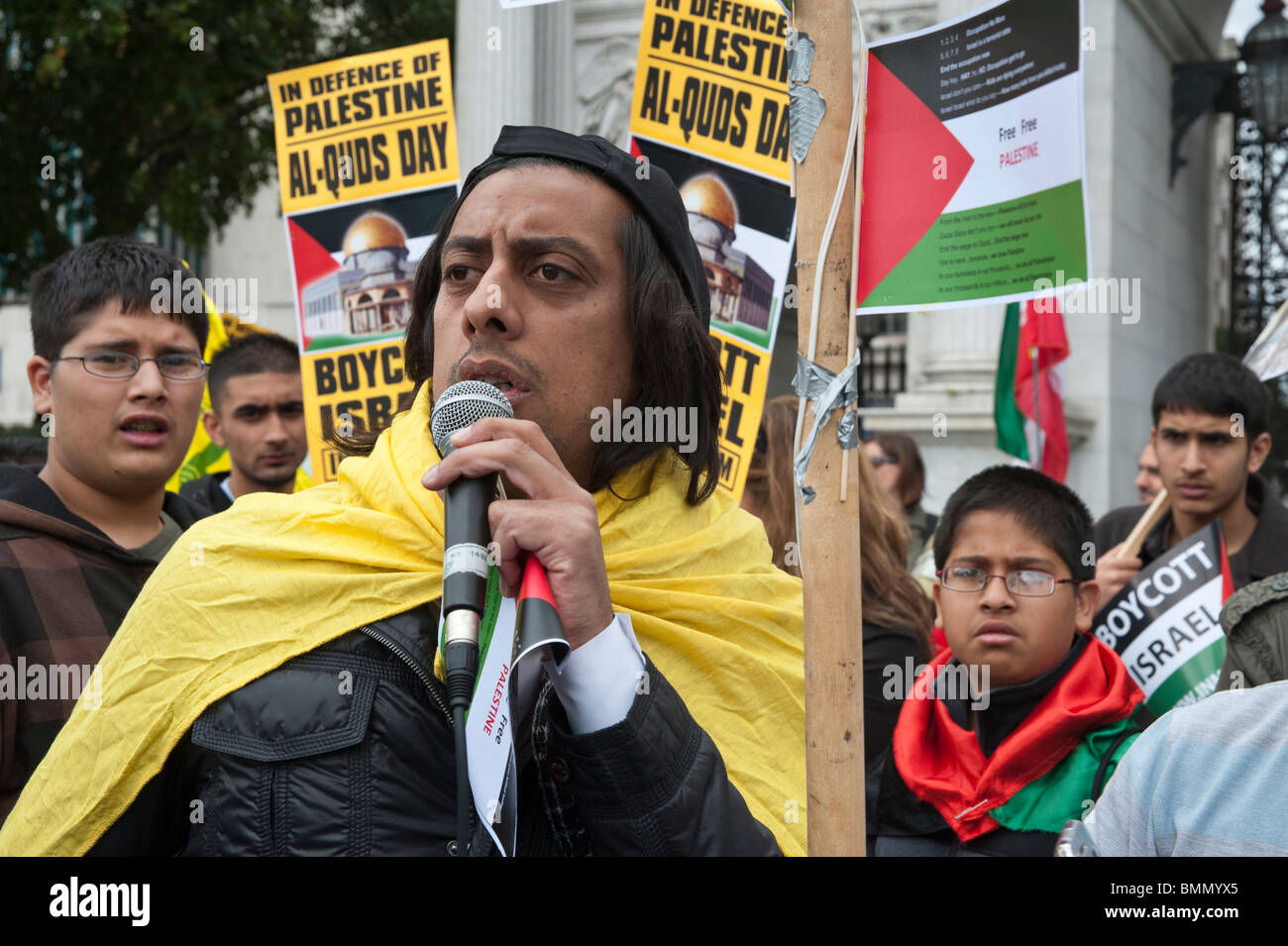 Muslim man speaking and placards at start of Al Quds Day (Jerusalem Day) march in London - Stock Image