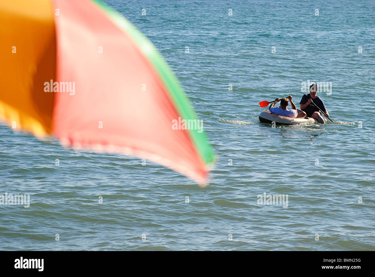 Boyspaddle in an inflatable boat off Charmouth Beach, Dorset, England - Stock Image