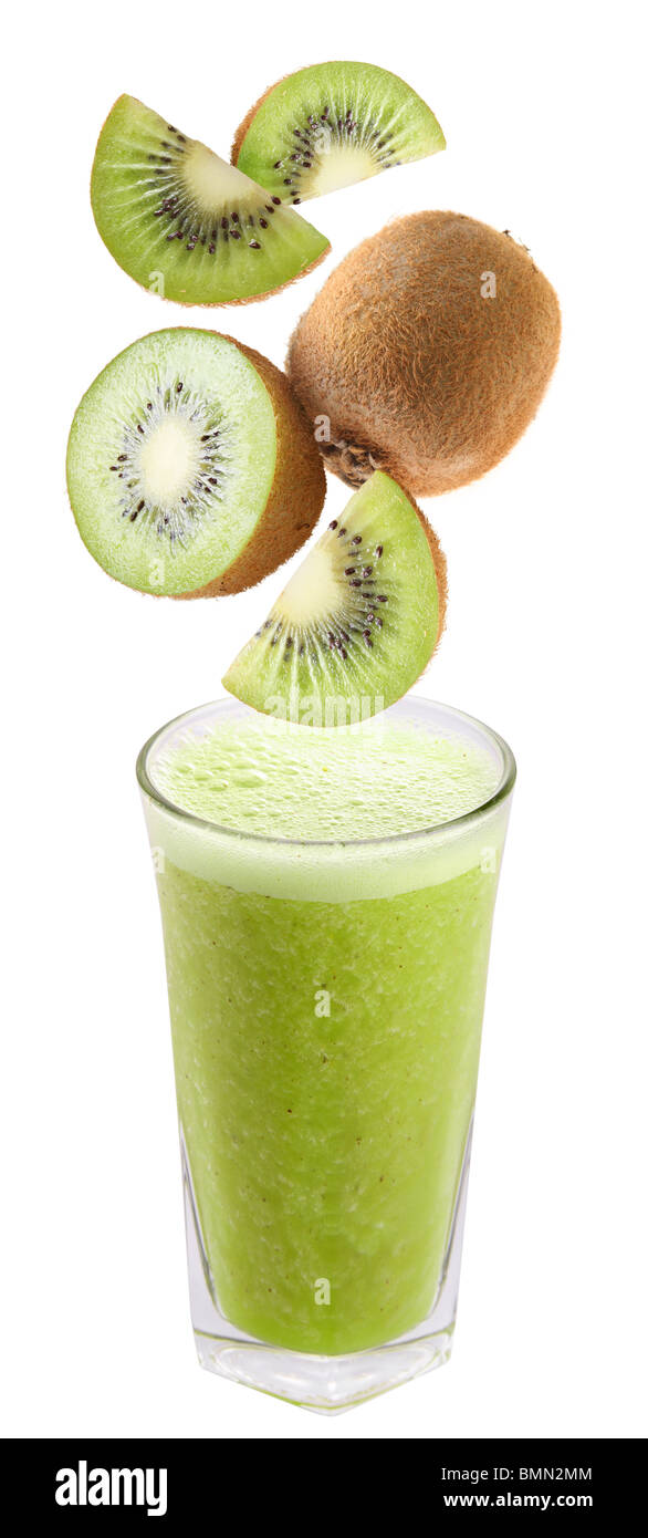 Slices of kiwi falling into a glass of fresh juice - Stock Image