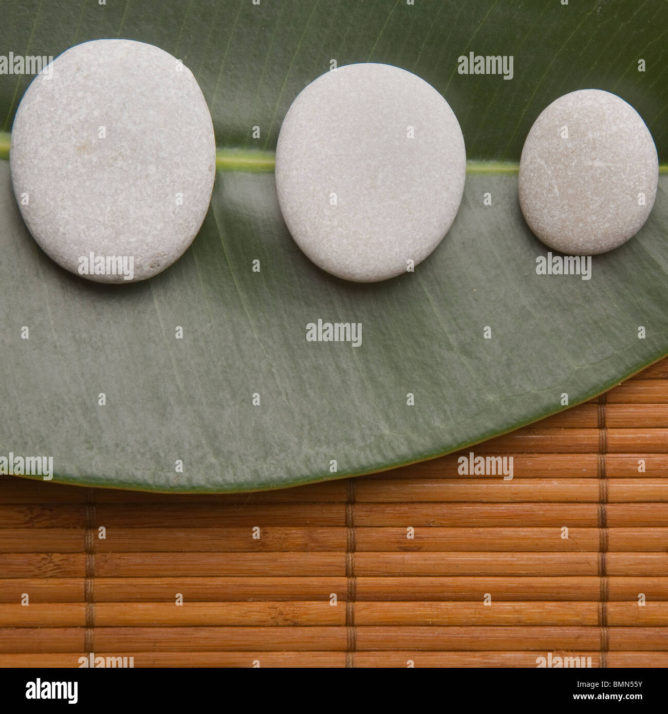 Three pebbles on a green leaf with a bamboo mat background - Stock Image