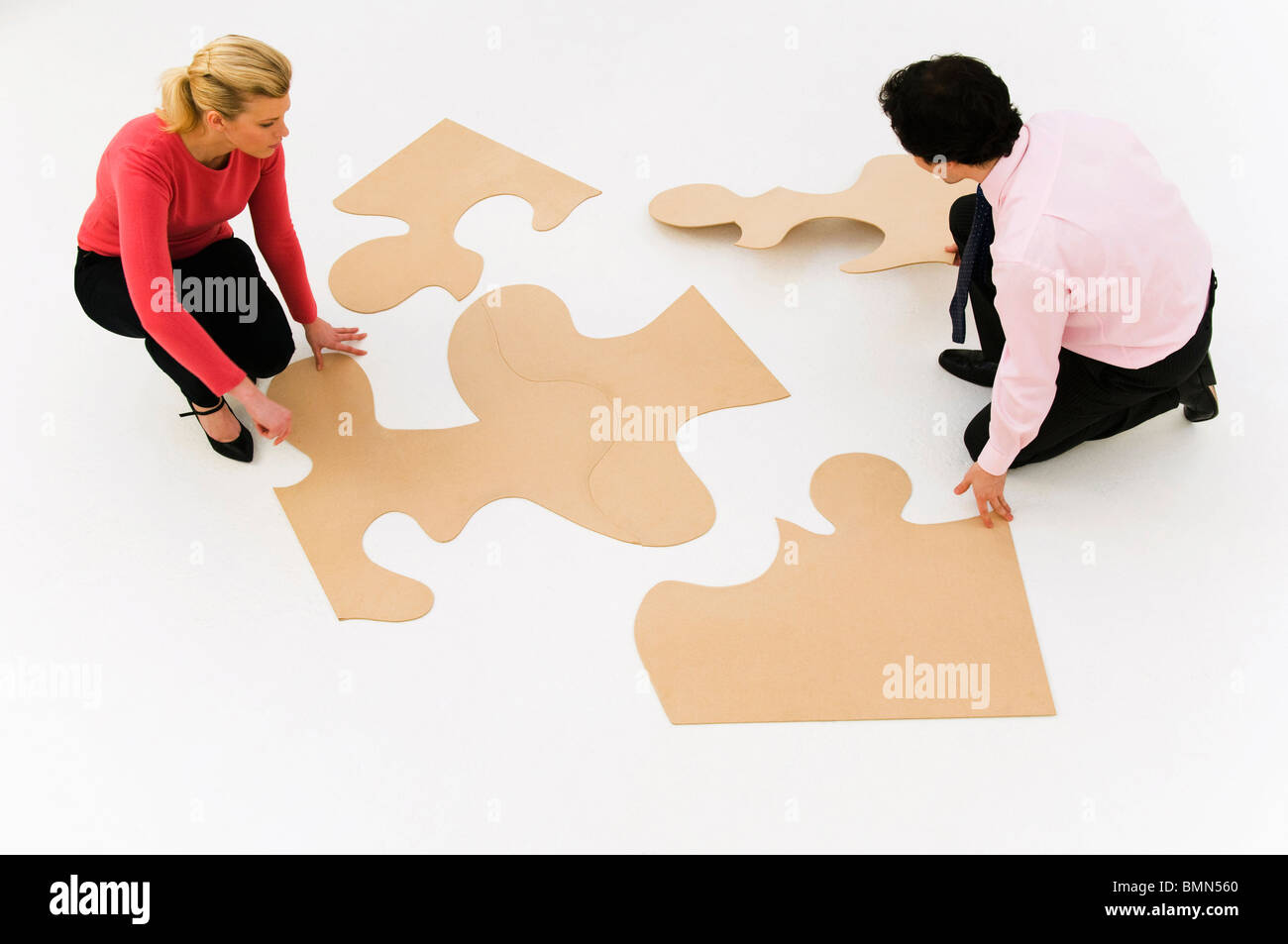Business people work at finishing puzzle Stock Photo