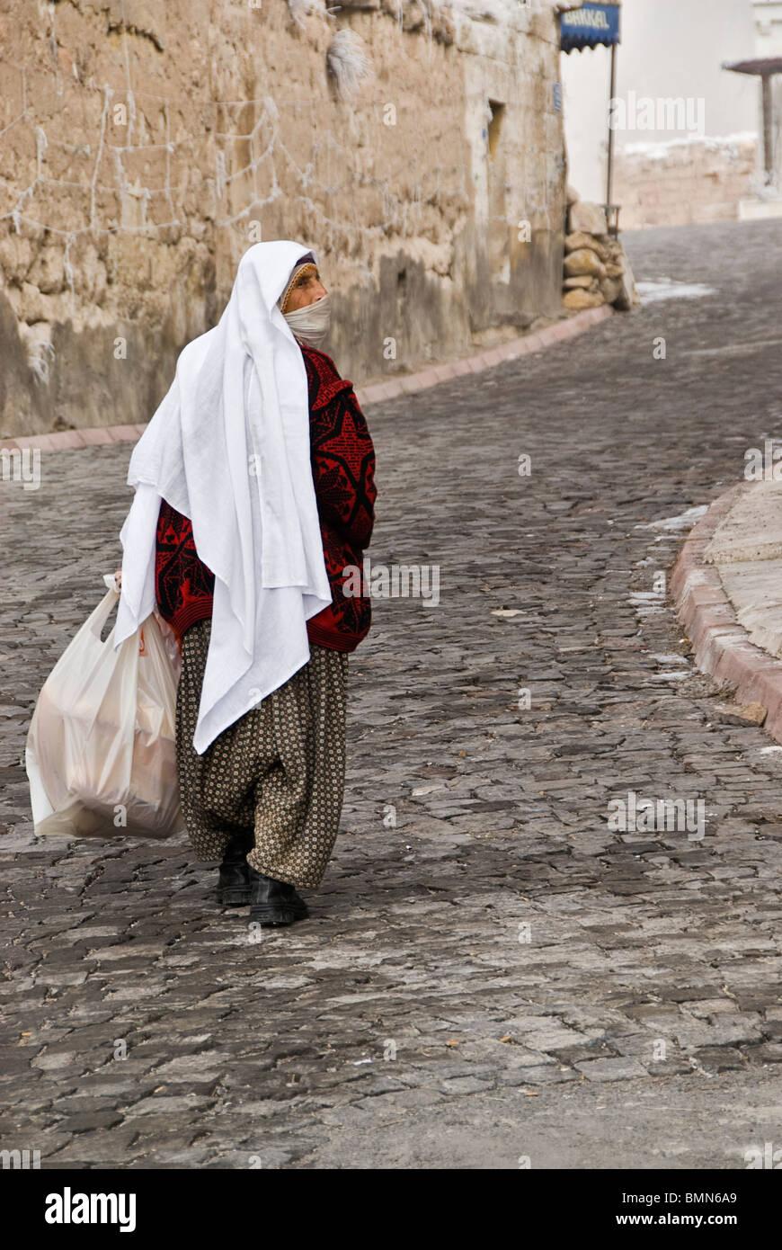 Old veiled woman walking on the streets. Capadoccia, Turkey, Asia. - Stock Image