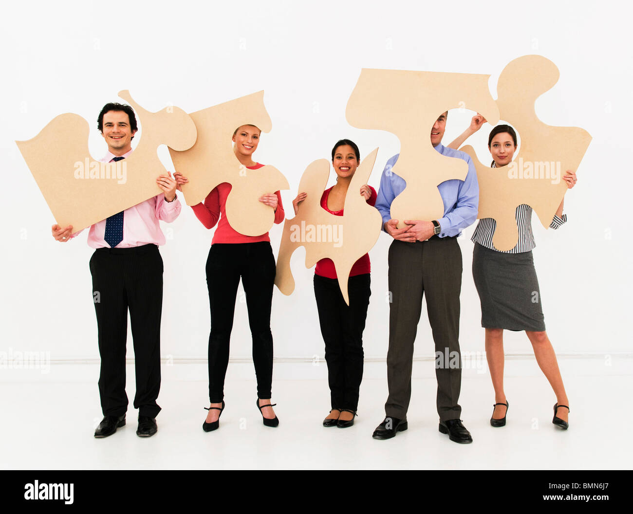 Team hold jigsaw pieces - Stock Image