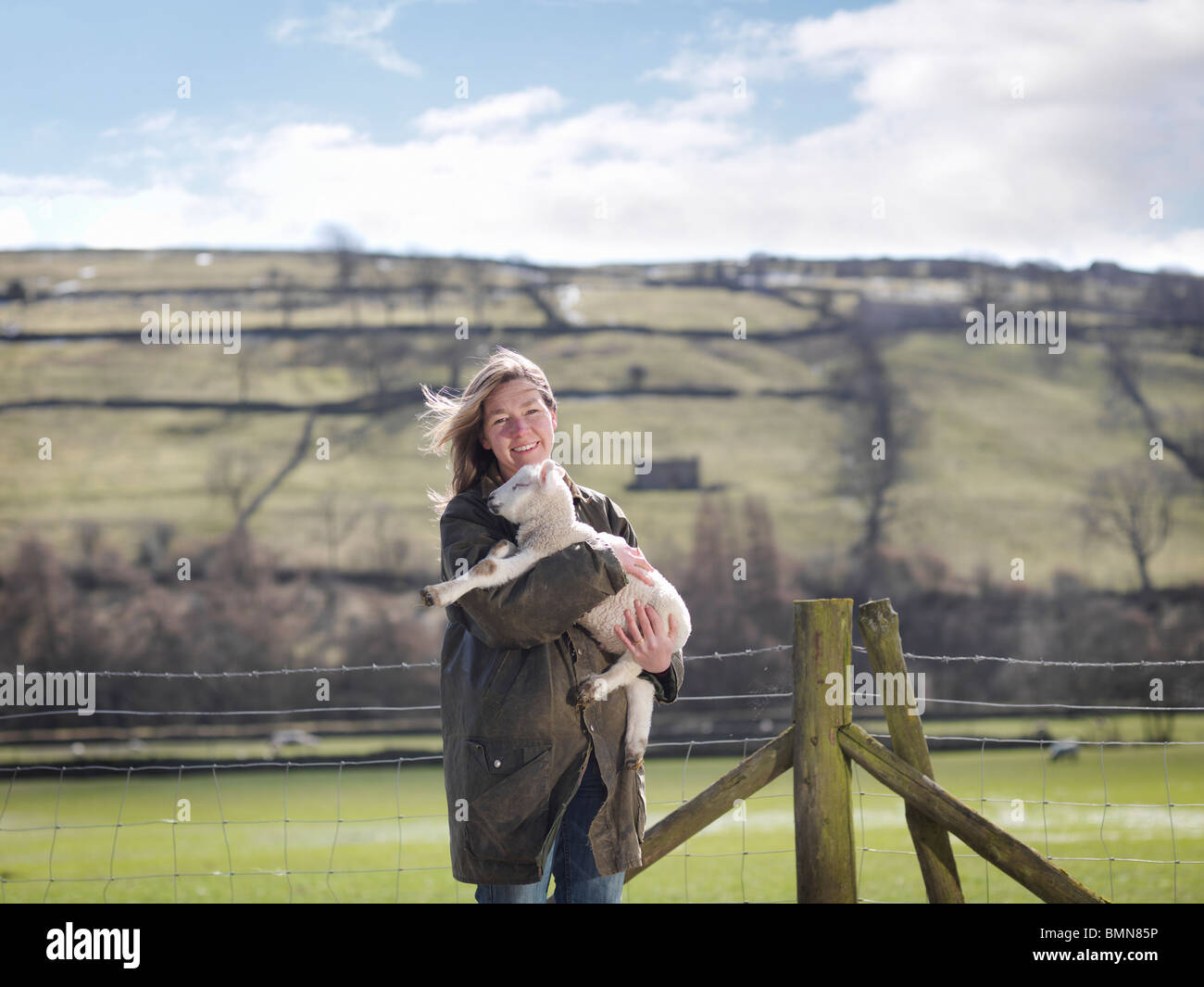 Woman holding lamb in front of fence Stock Photo