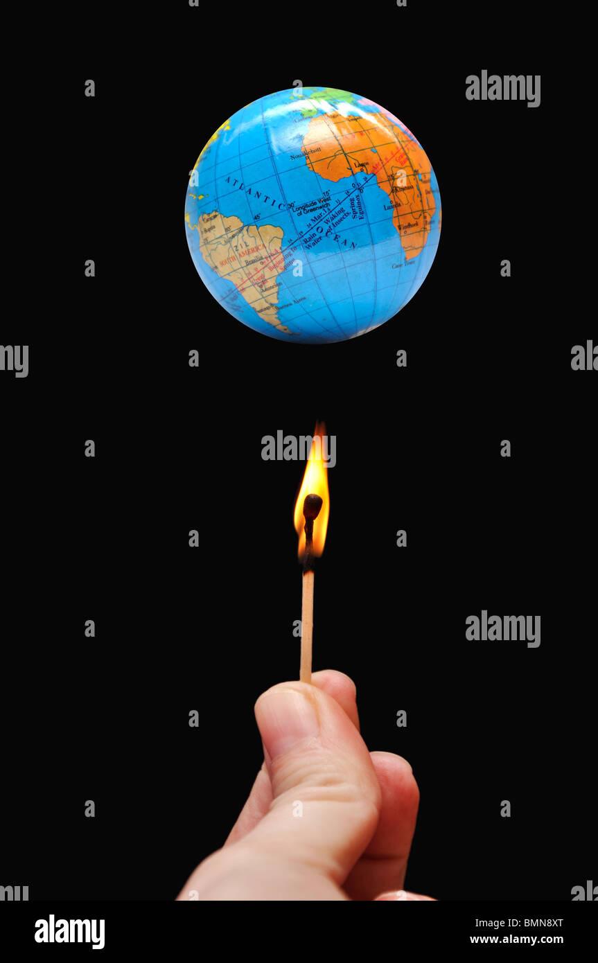 Woman lighting fire under globe - Stock Image