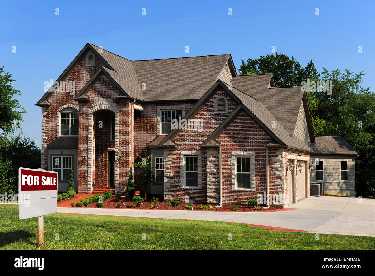 New house for sale with sign on front yard - Stock Image
