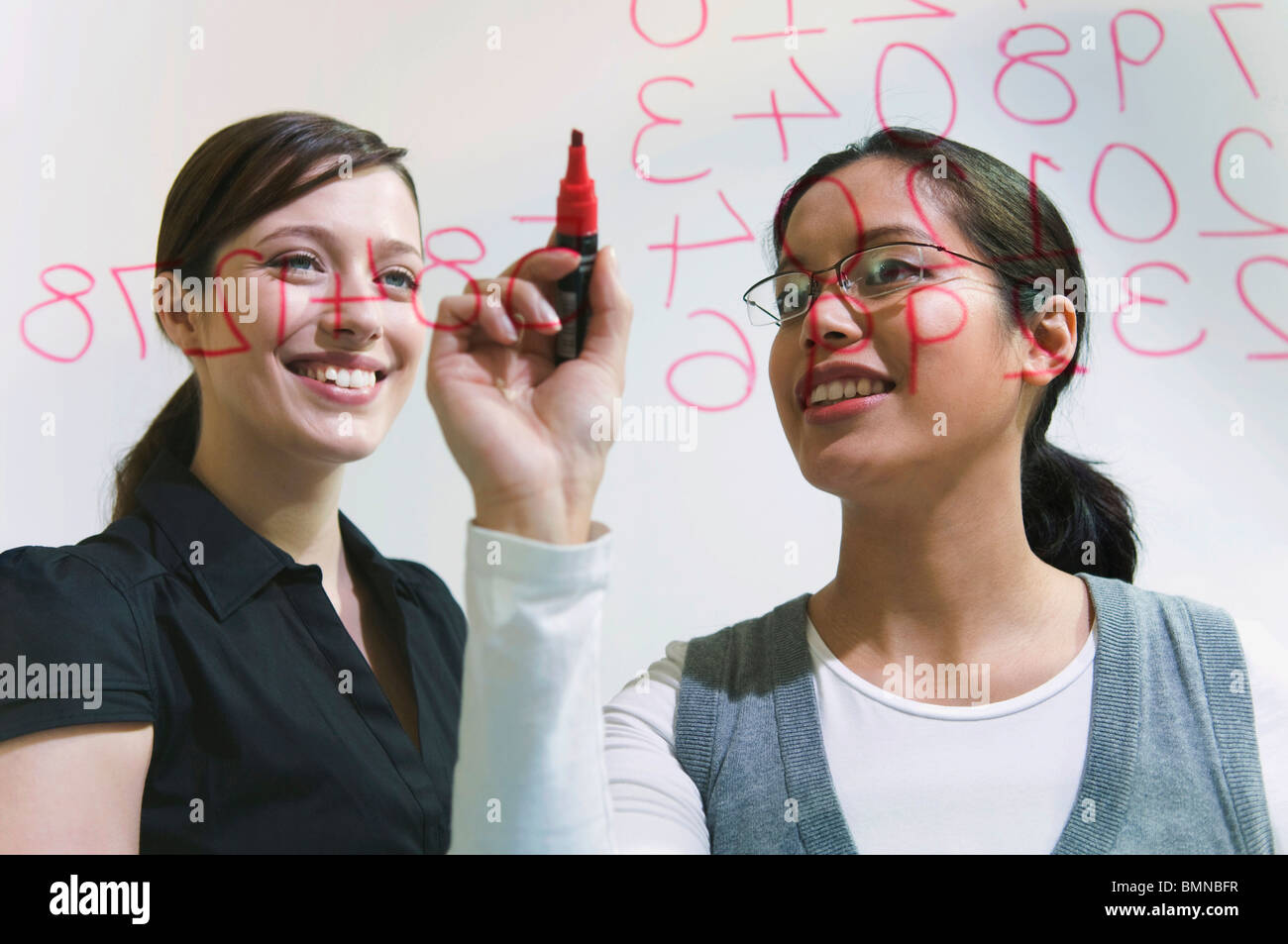 Two women work on figures on glass wall - Stock Image