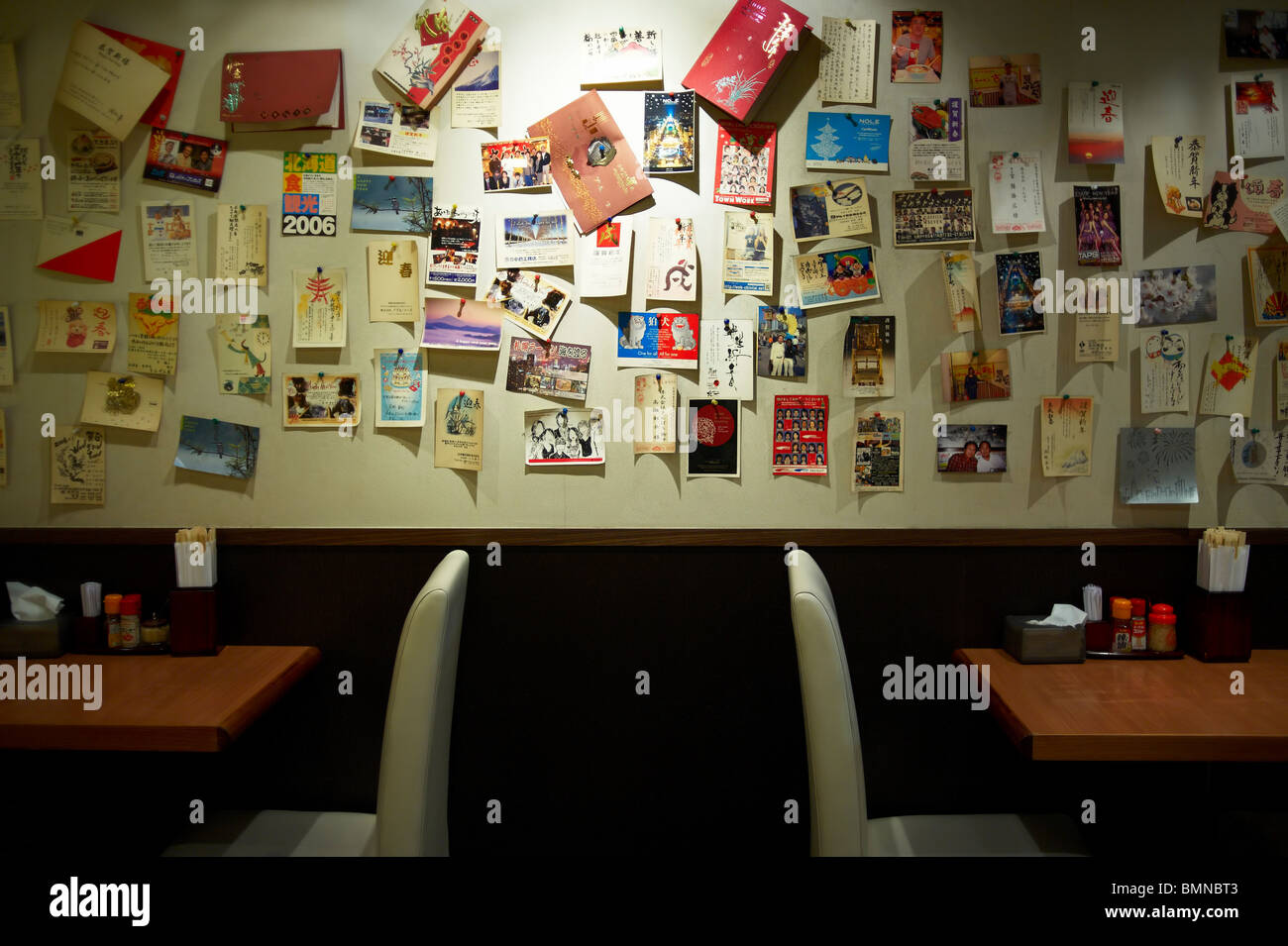 Postcards on the wall of a Japanese noodle bar hidden beneath the street in Kowloon from travelers around the world, Stock Photo