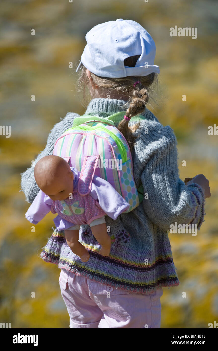 Girl with doll in the rucksack Farne Islands, Northumberland Coast, England, UK, Europe, June - Stock Image