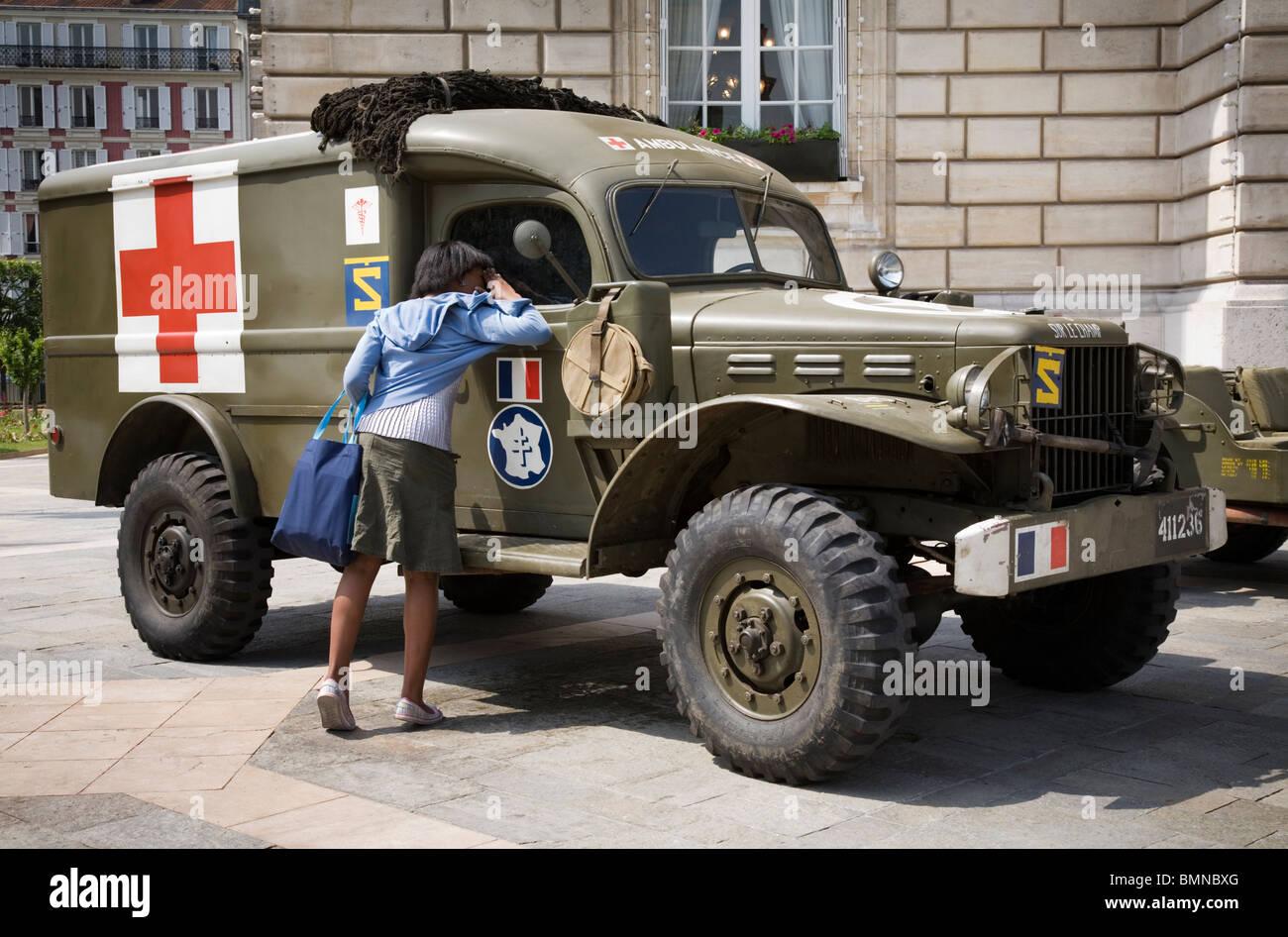A woman checking a WW2 vintage Ambulance, Paris - Stock Image
