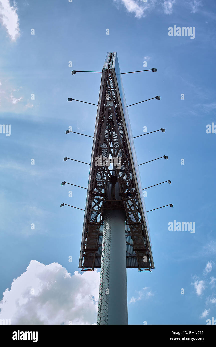 arrow shape advertising panel on the sky blue background with clouds - Stock Image