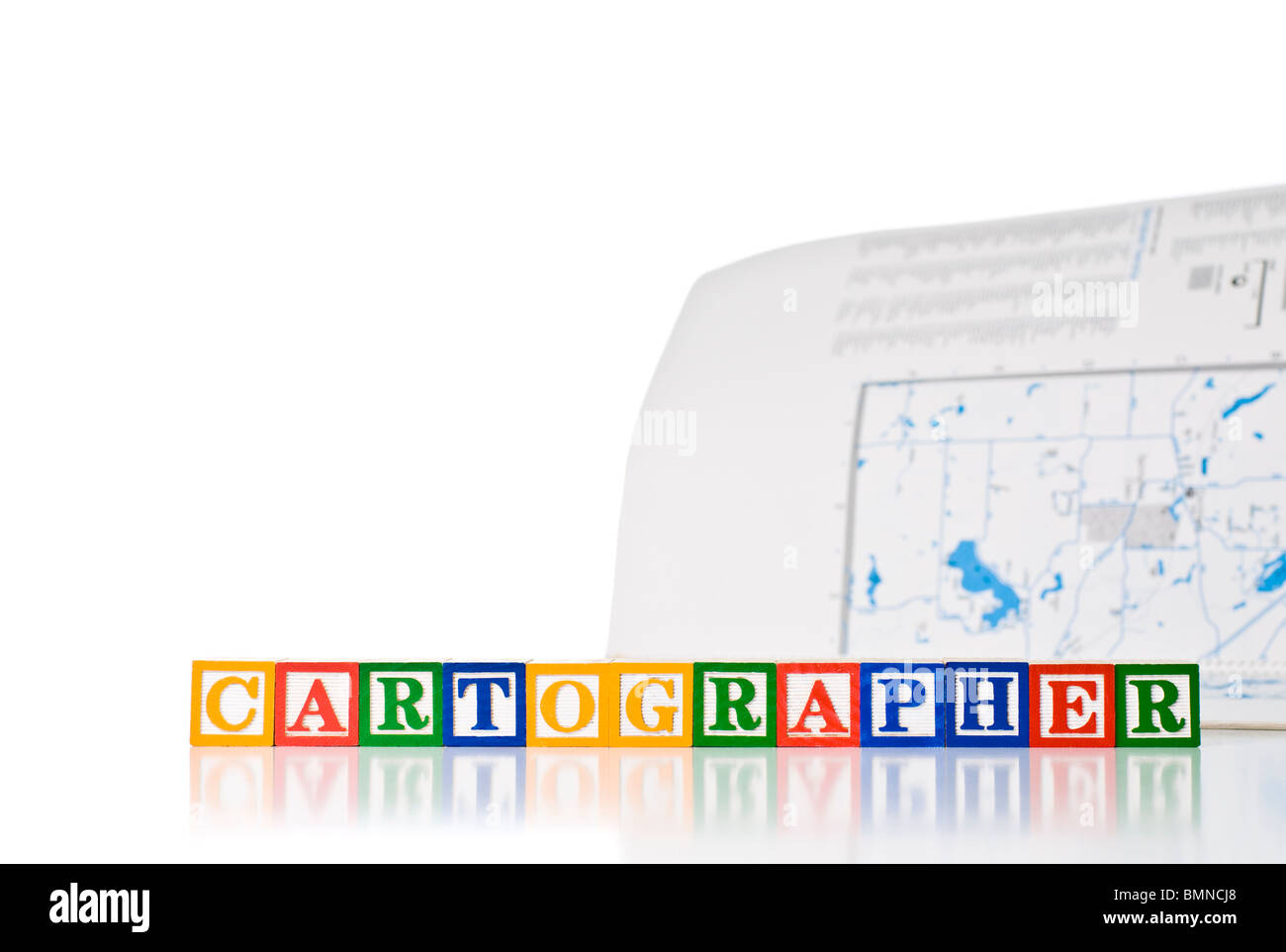 Colorful children's blocks spelling CARTOGRAPHER with a map - Stock Image
