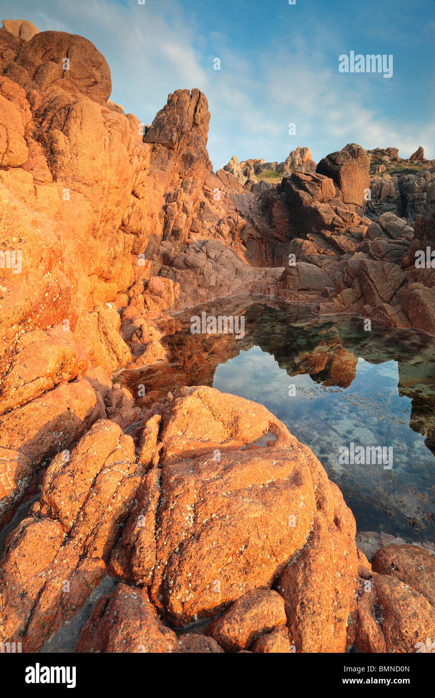 Reflections amidst the interesting geological formations of Albecg on the west coast of Guernsey - Stock Image