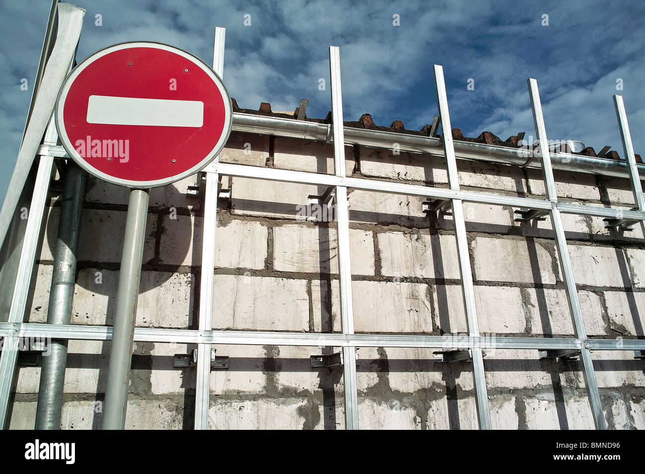 Red and white no entry road sign near the brick wall in midday time - Stock Image
