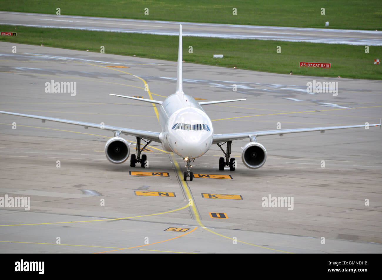 Large airplane taxiing to parking position at international airport - Stock Image