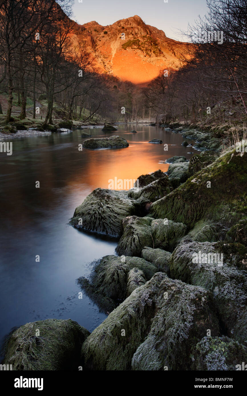 Alpenglow on High Crags as seen from the River Derwent just south of Keswick in the Lake District of England - Stock Image