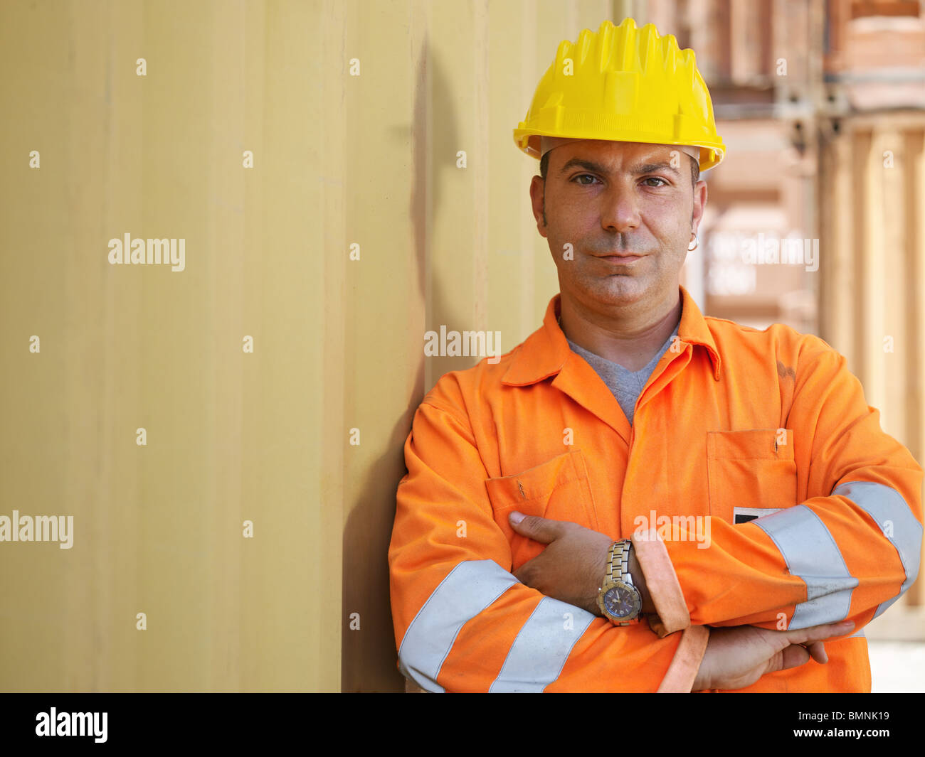 portrait of mid adult worker leaning on cargo container and looking at camera. Horizontal shape, front view, copy - Stock Image