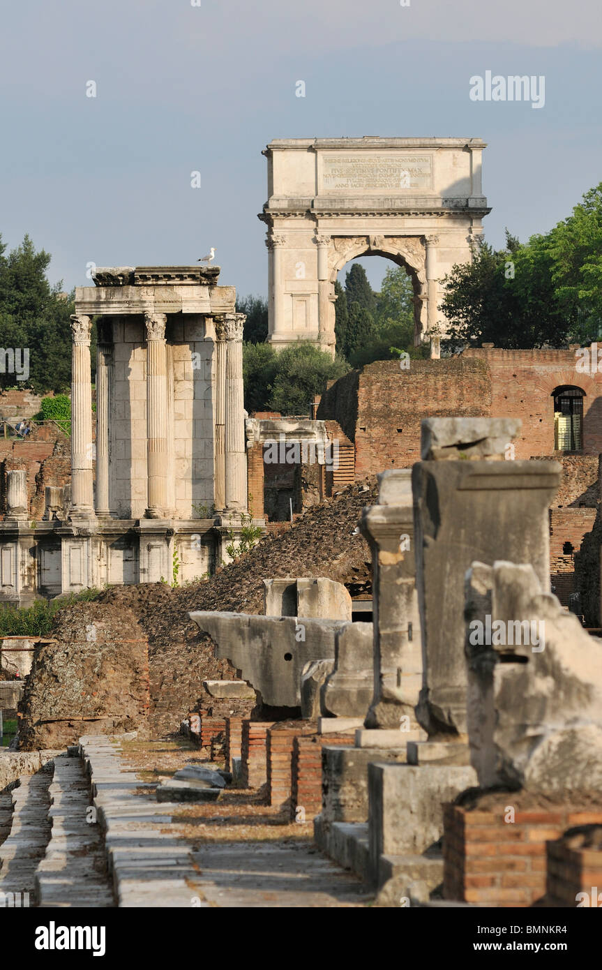 Rome. Italy. The Roman Forum (Foro Romano) Temple of Vesta (left) & Arch of Titus (right background) - Stock Image
