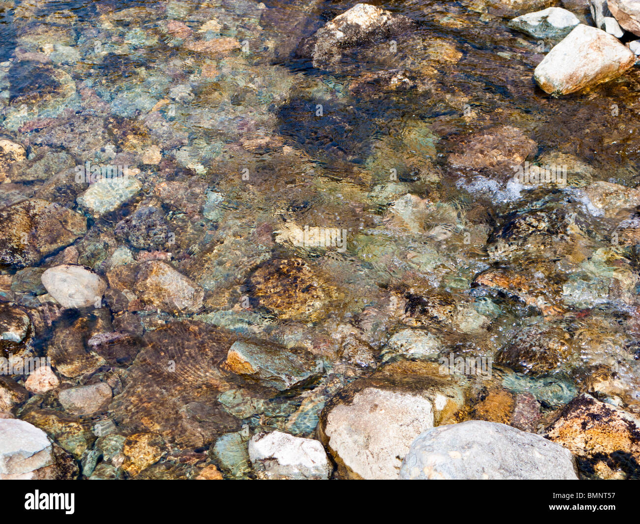 Pebbles in the water flowing in a stream close up overhead view - Stock Image