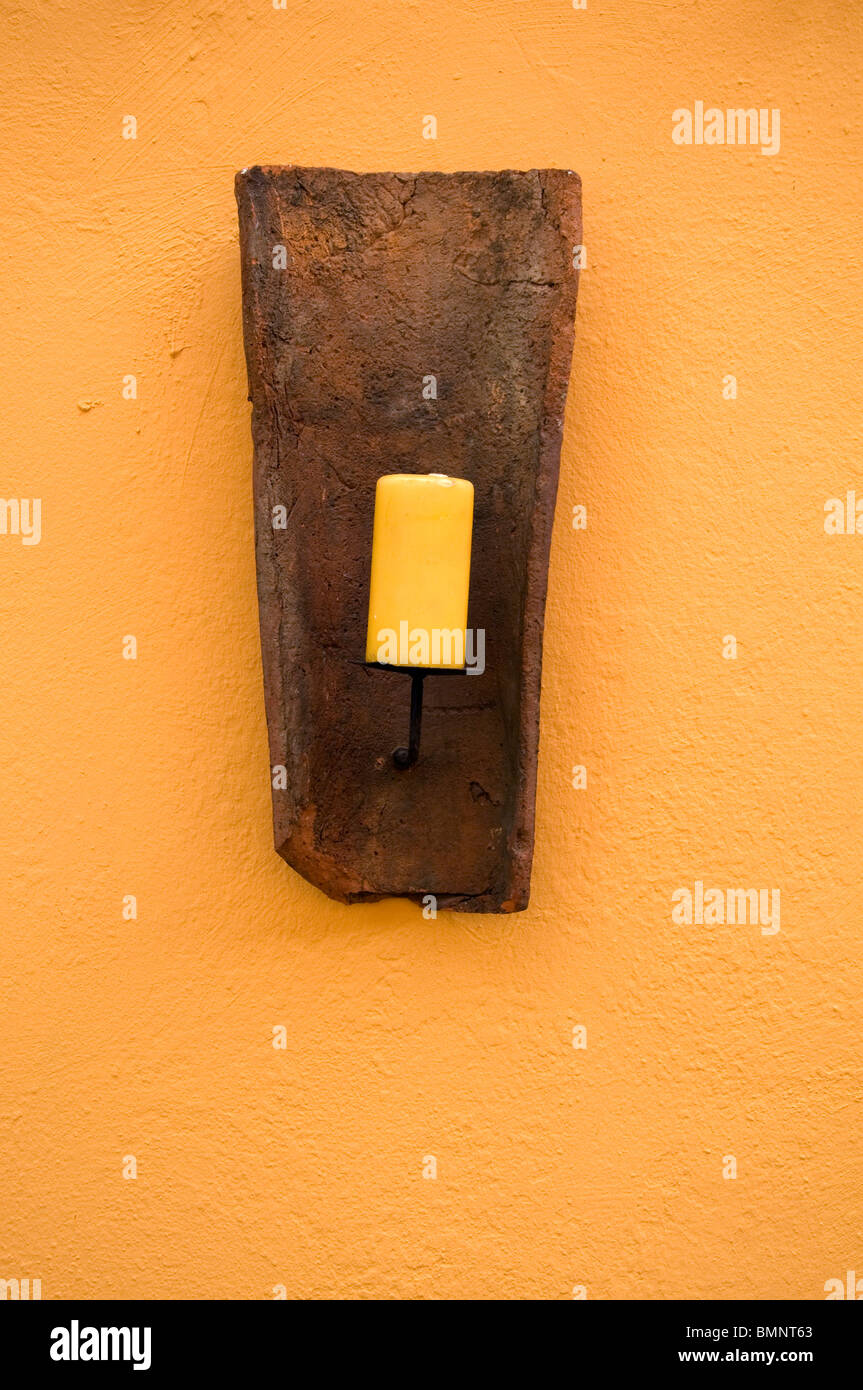 yellow candle in front of a yellow wall - Stock Image