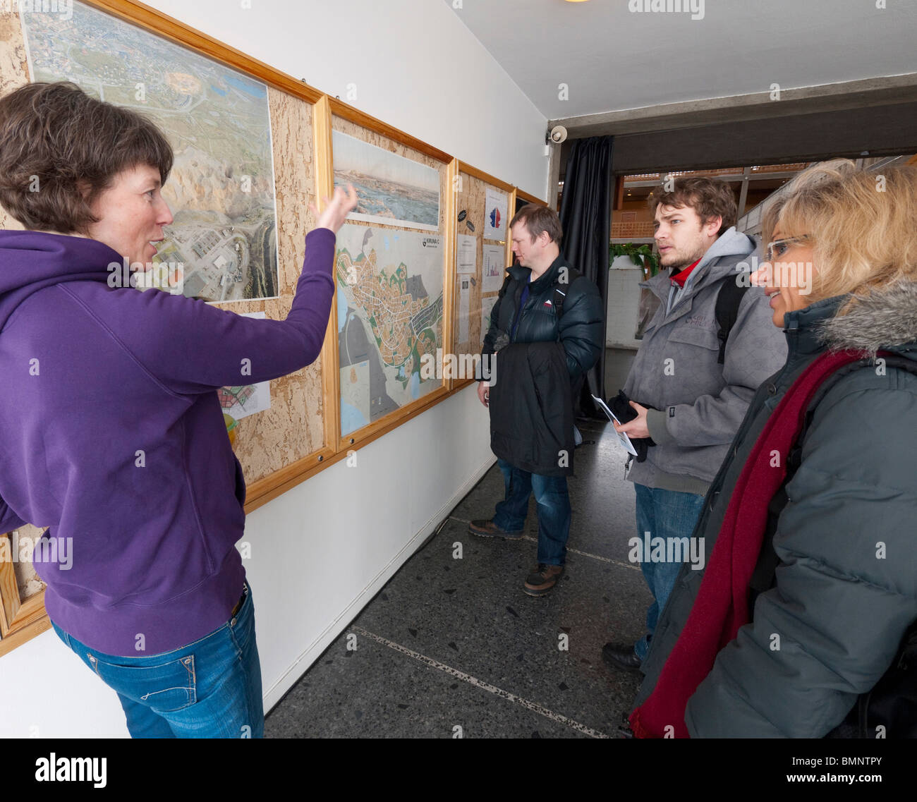 An employee of the city of Kiruna, left, explains the plans for the transformation of Kiruna to visitors in the - Stock Image