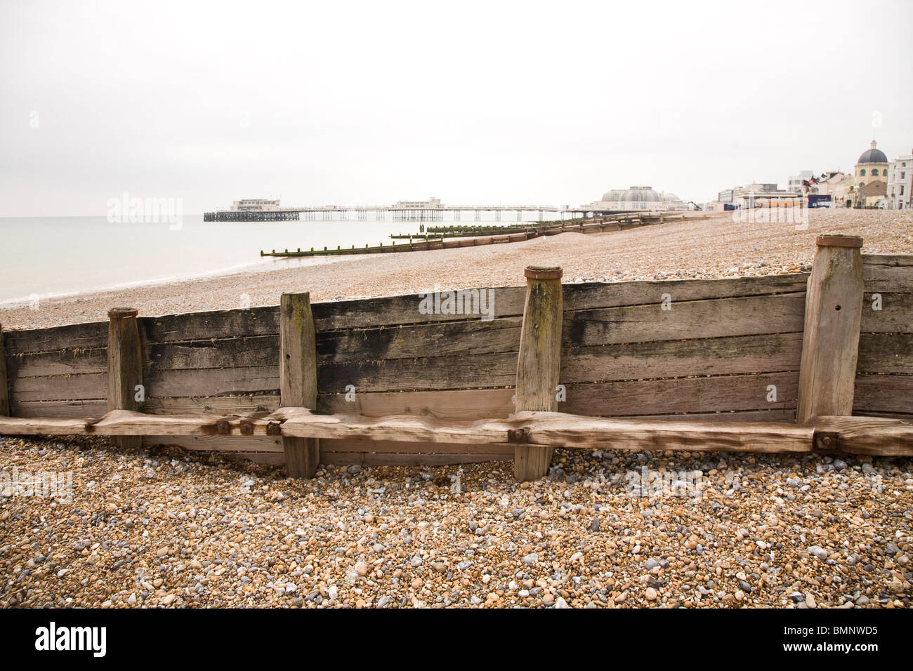 Breakwaters help prevent tidal erosion on the beach at Worthing in West Sussex, England. - Stock Image